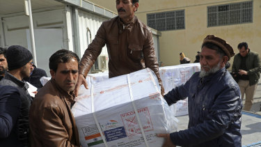 Afghan health ministry workers unload boxes of the first shipment of 500,000 doses of the AstraZeneca coronavirus vaccine made by Serum Institute of India.