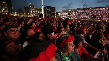 Spectators look on as French-Chilean singer Ana Tijoux performs during a concert by female artists on the eve of International Women's Day, in the Zocalo in Mexico City.