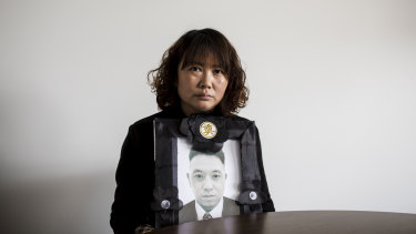 Lihong Wei holds a portrait of her husband Xiaojun Chen, who was killed while working for a delivery company in Sydney.