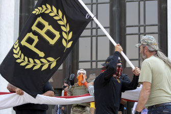 A protester carries a Proud Boys banner in front of the Oregon State Capitol in Salem.
