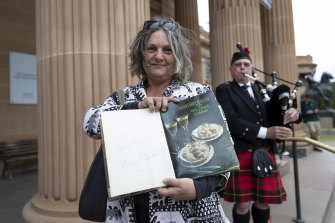 Maria Gunnerson-Briggs holds a signed copy of Margaret Fulton's cookbook outside the State Memorial Service for Margaret Fulton at the Art Gallery of NSW.