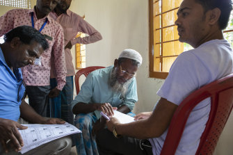 Farid Ali, a farmer (centre), looks in vain for his name on a list of verified citizens, in Shyampur, India. Lists of verified citizens were posted across the Indian state of Assam on Saturday. Those whose names did not appear — most of them Muslims — could soon be stateless.