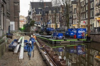 Construction workers rebuilding the crumbling canal wall in the Grimburgwal district of Amsterdam.