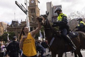 A man makes contact with a police horse during an anti-lockdown rally in the CBD.