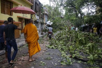 A Buddhist monk walks through a Kolkata road after Cyclone Amphan hit the city overnight on Wednesday May 20.