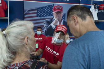 A vendor wearing a protective mask and shield speaks with customers ahead of Trump's rally in Tulsa.