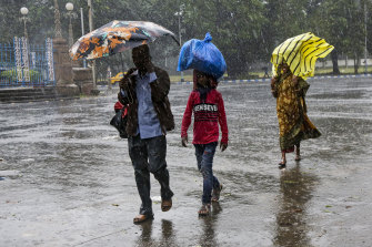Heavy rains from the cyclone hit Kolkata, India, on Saturday.