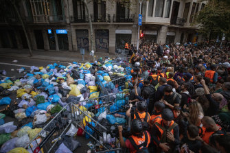 Catalan pro-independence demonstrators gather after dumping garbage bags in front of a government building.