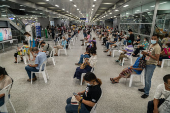 People wait in an observation area after being administered AstraZeneca at a vaccination centre at Bang Sue Grand Station in Bangkok.