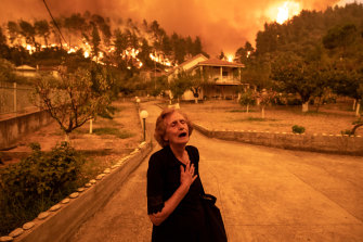 A woman despairs as a wildfire on the island of Evia approaches her house in the village of Gouves.