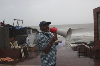 A municipal employee issues an evacuation warning by the shore of the Arabian Sea.