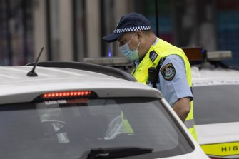 A police officer check's a driver's identification at a roadblock in Sydney.