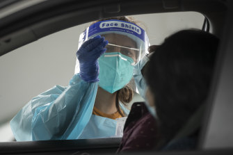 A health worker carries out a COVID-19 test at the Merrylands drive-through clinic in Sydney.