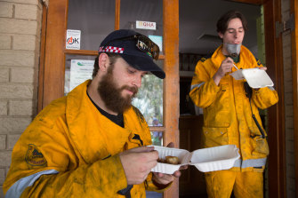 Firefighters eating lunch in the suburb of Noosa North Shore in Queensland on Wednesday.