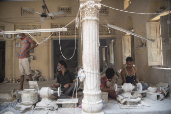 Craftsmen work at a marble inlay factory in Agra, India, June 24, 2021. The scarcity of visitors is a problem not only for Agra but also for the Archaeological Survey of India, the government agency that uses its share of the ticket sales to the Taj Mahal to restore and maintain many of the 3500 lesser-known but historically significant monuments from India's long, epic history.