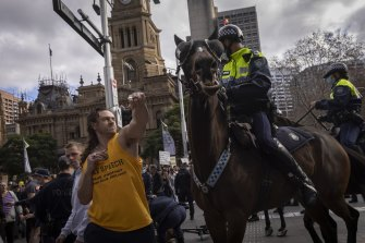 A man strikes a police horse during an anti-lockdown protest in Sydney on Saturday.