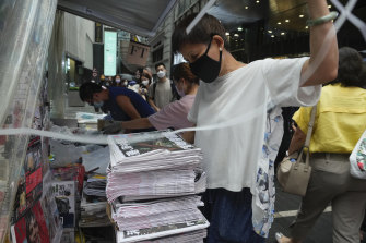 A vender adjusts a stack of last issue of Apple Daily at a newspaper booth in Hong Kong.