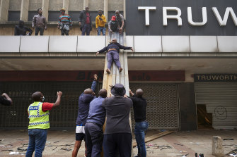 Children are evacuated from a burning building in downtown Durban, South Africa, on Tuesday July 13.