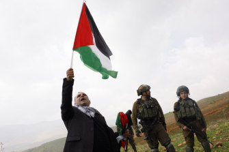 A man waves a Palestinian flag during a protest watched by Israeli soldiers near the Jewish settlement of Bekahot in the Jordan Valley, West Bank, on Wednesday.
