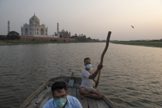 Sumit Chaurasia, left, a guide at the Taj Mahal, in front of the monument in Agra, India, in June, while on the Yamuna river, after the monument reopened.