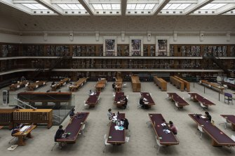 People work in the State Library of NSW as mask wearing becomes mandatory in certain indoor settings.