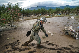 Rescue personnel walk over a sea of mud near an orchard in Nagano, Japan.