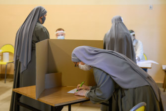 A nun wears a protective face mask as she casts her ballot during Poland's Presidential elections in Krakow, Poland.