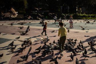 Children feed pigeons at Plaça Catalunya square in Barcelona.