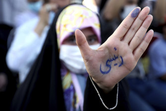 An Iranian voter shows the name Raisi written on her hand in Persian.