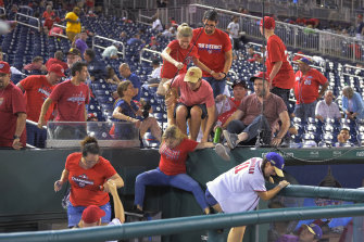Fans jump into a camera well after hearing gunfire from outside the stadium, during a baseball game between the San Diego Padres and the Washington Nationals.