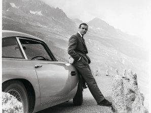 Sean Connery relaxes on the bumper of his Aston Martin DB5 during the filming for Goldfinger in the Swiss Alps.