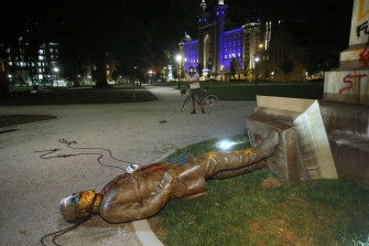 The statue of Confederate General Williams Carter Wickham lies on the ground after protesters pulled it down. The statue had stood in the park since 1891.