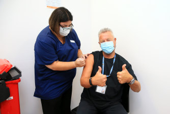 Dr Chris Quinn, who has been working in hotel quarantine, receives one of the first Pfizer COVID-19 vaccines at Austin Health, administered by nurse Jessica Amalfi.