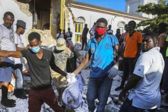 People carry away a body recovered from the rubble of an earthquake destroyed home in Les Cayes, Haiti.