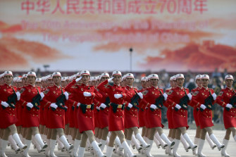 Chinese female militia members march in formation during a parade to commemorate the 70th anniversary of the founding of Communist China in Beijing.