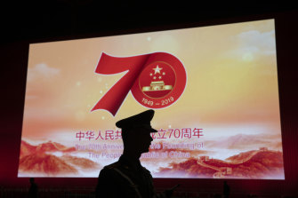 A Chinese paramilitary policeman is silhouetted by a display showing the upcoming 70th anniversary of the Founding of the People's Republic of China in Beijing.