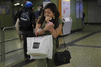 A woman emerges from a Hong Kong subway station after police used tear gas underground on Sunday night.