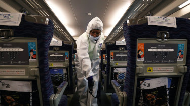 A disinfection worker in Seoul, South Korea, sprays anti-septic solution in a train amid rising public concerns over the spread of the coronavirus.