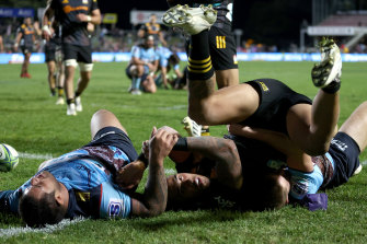 Sean Wainui scatters Waratahs defenders on the way to the line.