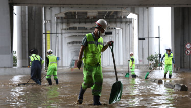 Workers begin the clean-up in the aftermath of a torrential storm that hit  Han River Park in Seoul.