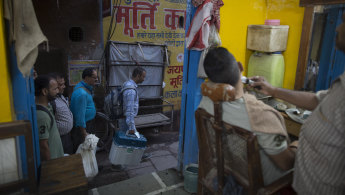 Election officers carrying electronic voting machines walk past a barber shop at the close of polling in Varanasi, India on Sunday.