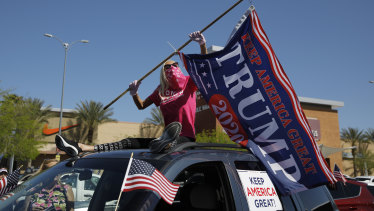A woman holds a Donald Trump flag to protest the closing of businesses and stay-at-home orders due to the coronavirus in Las Vegas.