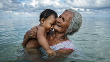 Suega Apelu bathes a child in the lagoon in Funafuti, Tuvalu. The low-lying South Pacific island nation of about 11,000 people has been classified as extremely vulnerable to climate change by the United Nations Development Programme.