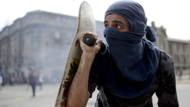 An anti-government protester peers out from behind his skateboard during clashes with police in Valparaiso.