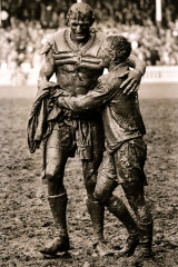 The Gladiators ... Norm Provan, left and Arthurs Summons hug in the mud after the 1963 grand final.