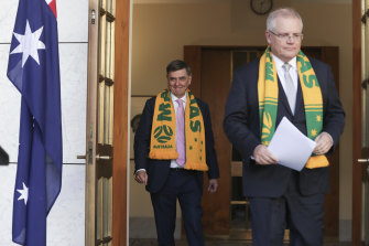 Chief Medical Officer Professor Brendan Murphy and Prime Minister Scott Morrison arrive wearing Matildas scarves as they address the media at Parliament House in Canberra on Friday.