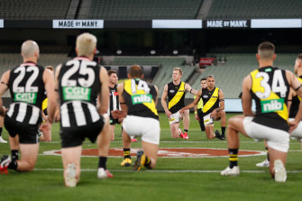 Players take a knee to support the Black Lives Matter movement at the MCG.