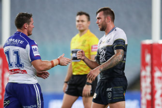 Bulldogs captain Josh Jackson goes to shake hands with Kyle Feldt but the Cowboys winger opts for a safer approach.