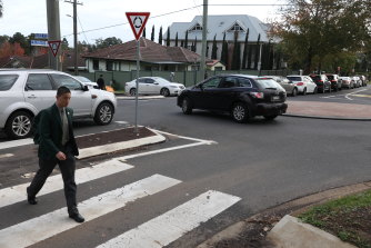 A student crosses the road as cars queue for the pick-up zone at James Ruse and Carlingford West Public School.