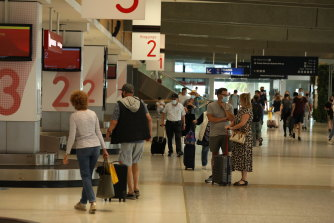 Passengers collect their bags after flying into Sydney from Melbourne on Qantas Flight 450 on Friday.
